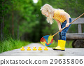 Funny little girl playing with five rubber ducklings 29635806