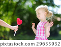 Cute little girl eating huge heart-shaped lollipop outdoors 29635932