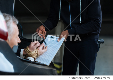Unhappy senior man being forced to sign the 29637979