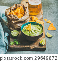 Fresh guacamole sauce in blue ceramic bowl, corn 29649872
