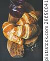 Freshly baked croissants with raspberry jam in jar 29650041