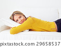 Woman in yellow sweater lying on a white sofa 29658537