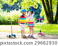 Kids riding scooter in summer park. 29662930