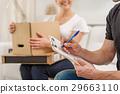 Deliveryman sitting on sofa near woman 29663110