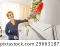 Joyful woman cleaning room with broom 29663187