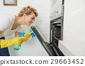 Concentrated female person looking at stove 29663452