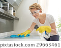 Happy housewife wiping kitchen stove 29663461