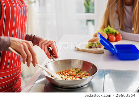 Woman frying vegetables with her kid 29663554