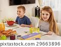 Happy kids eating sweet waffles in kitchen 29663896