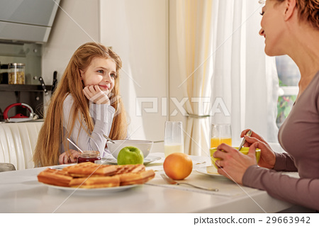 Cute mother and daughter having healthy breakfast 29663942