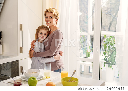 Cheerful girl embracing her mom at home 29663951