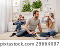 Joyful parents playing with their children at home 29664097