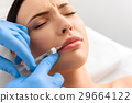 Concerned female feeling anguish during injection 29664122