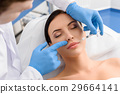 Satisfied woman receiving injection in face 29664141
