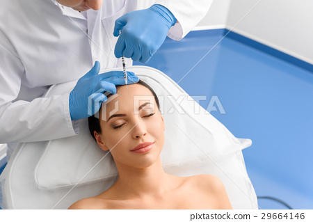 Smiling woman receiving treatments in beauty salon 29664146