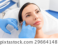 Serene woman receiving cosmetic procedure 29664148