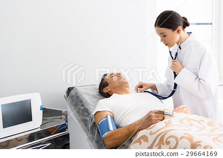 Calm female doctor listening male by stethoscope 29664169