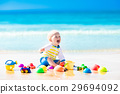 Baby playing on tropical beach digging in sand 29694092