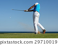 Golfer hitting ball with force. The grass distribu 29710019