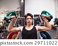 Hispanic man training in gym, doing machine 29711022