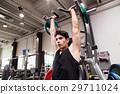 Hispanic man training in gym, doing machine 29711024