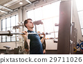 Fit young man in gym working out, lifting barbell 29711026