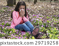Cute girl blowing her nose among primroses 29719258