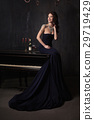 beautiful young woman in black dress  piano 29719429