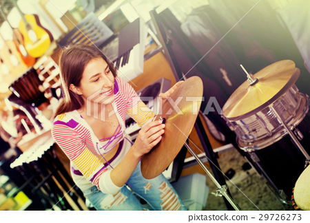 Happy smiling teenage girl shopping drum kit in studio 29726273