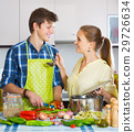 man and woman standing near table in domestic kitchen 29726634