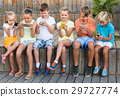 Group of children playing with mobile phones outdoors 29727774