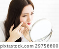 woman squeeze her acne in front of the mirror 29756600