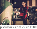 Woman among retro cars in garage 29763189