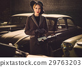 Woman among retro cars in garage 29763203