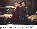 Two women among retro cars in garage 29763213