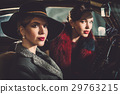 Two women among in a retro car in garage 29763215