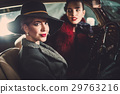 Two women among in a retro car in garage 29763216