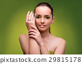 Young woman in beauty concept on green background 29815178