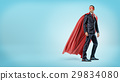 A businessman in a flowing red superhero cape and 29834080