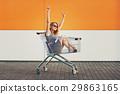 beautiful blonde girl sitting in shopping basket 29863165