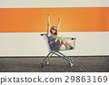 beautiful blonde girl sitting in shopping basket 29863169