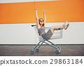 beautiful blonde girl sitting in shopping basket 29863184