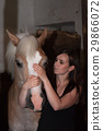 Young woman stroking her horse in stable. 29866072