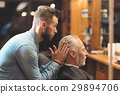 Stylish barber shaping haircut of the client in 29894706