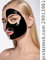 Girl takes off black cosmetic mask from her face. 29913961