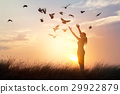 Woman praying and flying birds on sunset  29922879
