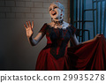 Woman in a red dress with a vampire grin. 29935278