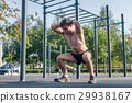 Muscular fitness athlete doing squats with his 29938167