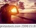 Tourist woman watching sunset at tropical beach 29961518