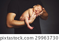 Newborn baby in his father's hands in dark 29963730